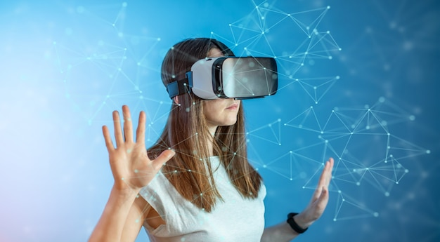 Eine junge frau, die eine brille der virtuellen realität trägt, die an einer 3d-visualisierung in einem abstrakten polygonalen gitter auf einem blauen hintergrund in einem futuristischen stil beobachtet