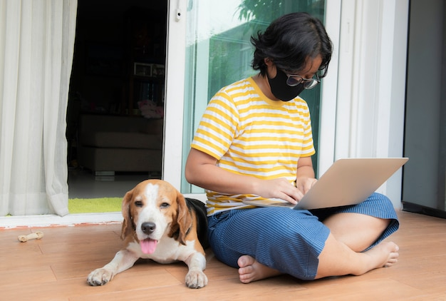 Eine junge frau, die eine maske trägt, die ein notizbuch vor dem haus mit einem beagle-hund trägt, der daneben sitzt