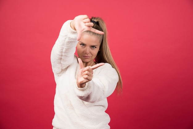 Eine junge frau, die einen pullover trägt, zeigt etwas kleines mit den händen