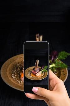 Eine junge frau, die essen auf dem smartphone fotografiert und essen mit einer mobilen kamera fotografiert. gemacht für soziale netzwerke. handy von oben