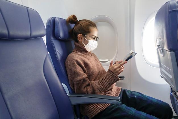 Eine junge frau, die gesichtsmaske trägt, reist im flugzeug, neues normales reisen nach covid-19-pandemiekonzept