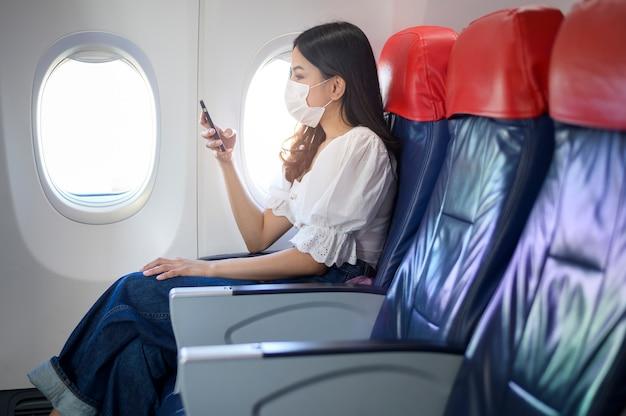 Eine junge frau, die gesichtsmaske trägt, verwendet smartphone an bord, neues normales reisen nach covid-19-pandemiekonzept