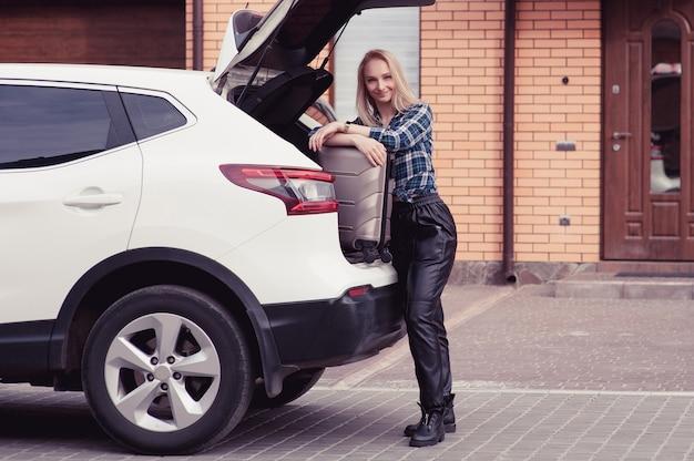 Eine junge frau, die ihr gepäck in den kofferraum eines autos steckt
