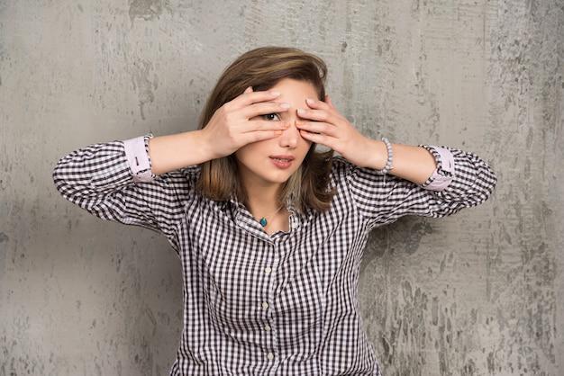 Eine junge frau, die ihre augen mit ihren händen mit einer schönen maniküre bedeckt