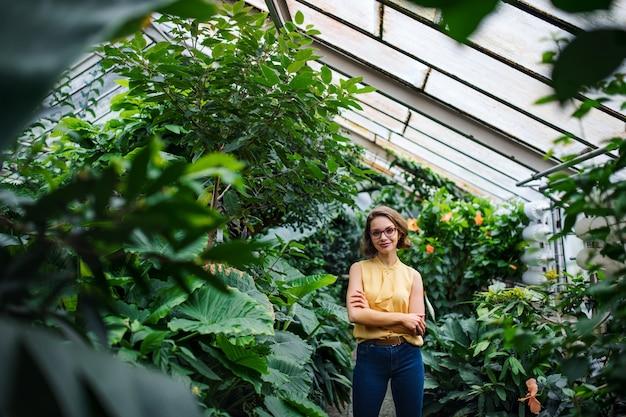 Eine junge frau, die im gewächshaus im botanischen garten steht. platz kopieren.