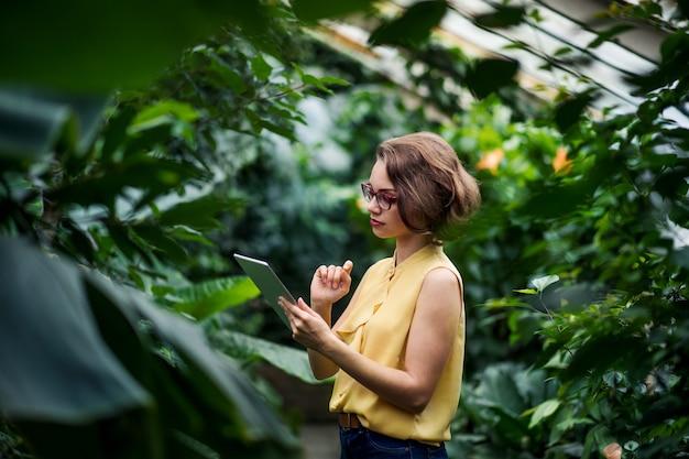 Eine junge frau, die im gewächshaus im botanischen garten steht und tablet verwendet.