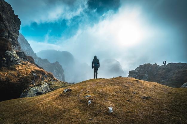 Eine junge frau, die im morgengrauen auf dem berggipfel von aiako harriak, oiartzun, die spitze im nebel erklimmt. baskenland