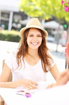 Eine junge frau, die im sommer im café sitzt