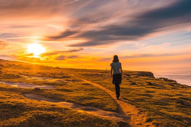 Eine junge frau, die im sonnenuntergang von jaizkibel geht. baskenland