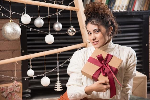 Eine junge frau, die in die kamera schaut und eine geschenkbox mit schleife hält
