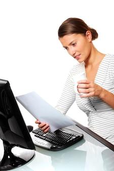 Eine junge frau, die in ihrem büro beschäftigt ist