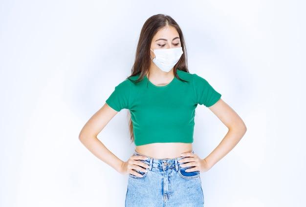 Eine junge frau, die in medizinischer schutzmaske steht und mit den händen auf den hüften posiert.