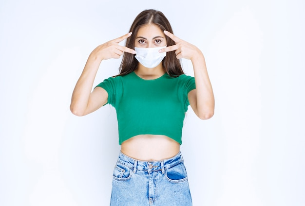 Eine junge frau, die in medizinischer schutzmaske steht und siegeszeichen zeigt.