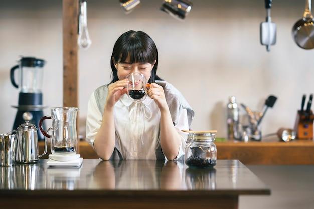 Eine junge frau, die in ruhiger atmosphäre kaffee brüht und trinkt