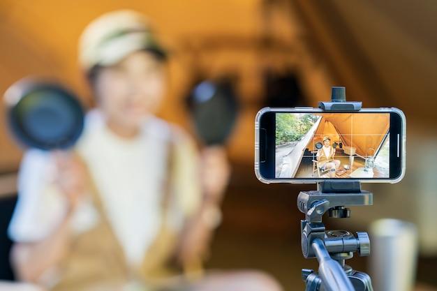 Eine junge frau, die mit ihrem smartphone in einem zelt campt und fotografiert shooting