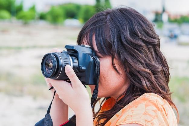 Eine junge frau, die mit reflexkamera fotografiert