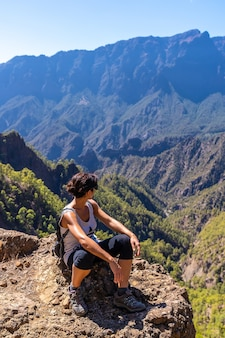 Eine junge frau, die nach dem wandern auf la cumbrecita ruht, sitzt im natürlichen aussichtspunkt, der die berge der caldera de taburiente, insel la palma, kanarische inseln, spanien betrachtet
