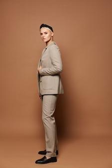 Eine junge frau, die offizielle kleidung trägt, die auf einem beigefarbenen hintergrund isoliert ist, modell blondes mädchen in modischem anzug, isoliert im hintergrund mit kopienraum