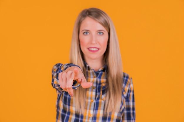 Eine junge frau, die seinen finger in richtung zur kamera gegen einen orange hintergrund zeigt