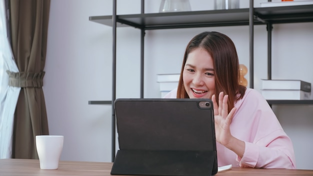 Eine junge frau, die videoanruf mit familie auf tablet-computer zu hause hat.