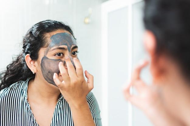 Eine junge frau, die vor einem spiegel in ihrem badezimmer eine gesichtsmaske aufsetzt