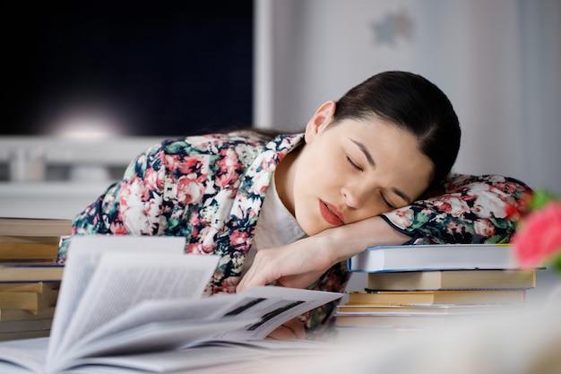 Eine junge frau, die vor einem stapel papiere schläft