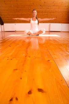Eine junge frau, die yoga in einem dachbodenstudio praktiziert.