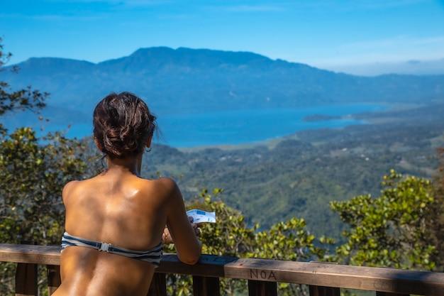 Eine junge frau, die yojoa see vom mirador del cerro azul meambar nationalpark (panacam) beobachtet. honduras
