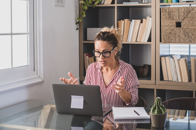 Eine junge frau, die zu hause im büro mit laptop und notebook arbeitet und notizen macht, die in einer videokonferenz sprechen. eine geschäftsfrau, die kommunikation anruft