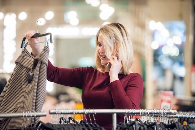 Eine junge frau erhält einen anruf in einem einkaufszentrum