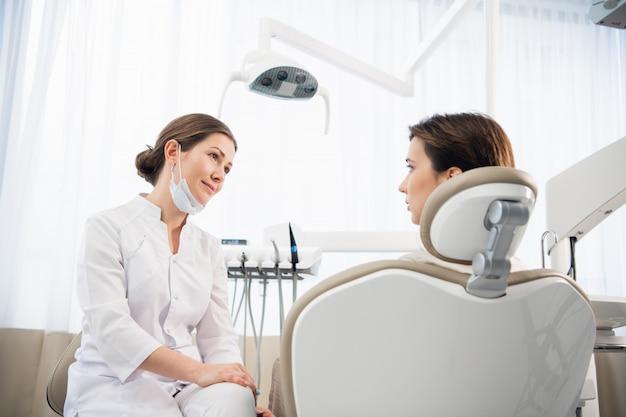 Eine junge frau erklärt ihrem arzt, der aufmerksam zuhört, ihr zahnproblem