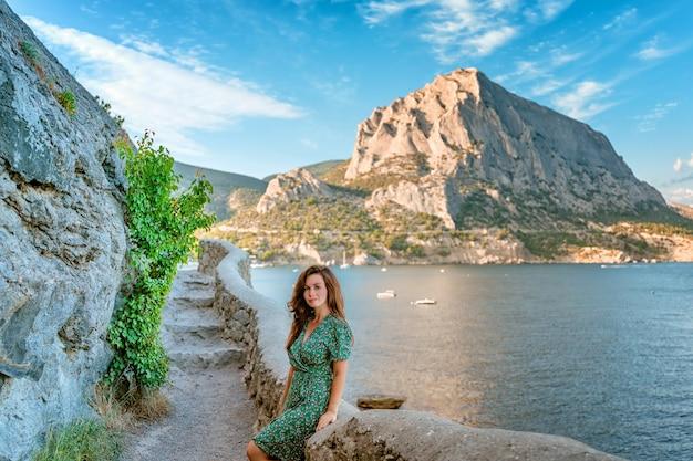 Eine junge frau geht den golitsyn-pfad entlang mit blick auf die berge und die meereslandschaft i