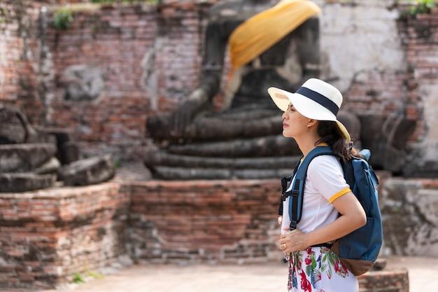 Eine junge frau geht in den alten tempel in phra nakhon si ayutthaya, thailand an einem entspannenden tag.