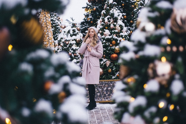 Eine junge frau geht zu weihnachten auf dem platz in der nähe der geschmückten weihnachtsbäume. candy ist ein lutscher in form eines herzens.