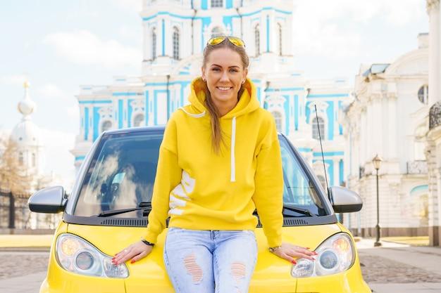 Eine junge frau, gekleidet in ein helles sweatshirt und jeans, stützt sich auf ihr gelbes auto und lächelt draußen.