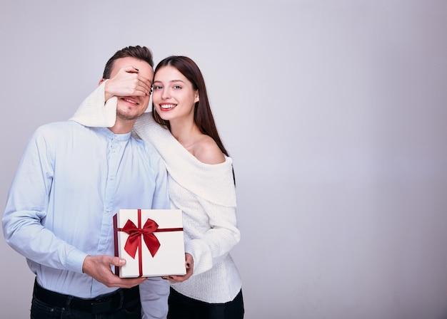 Eine junge frau gibt einem mann ein geschenk und schließt die augen.