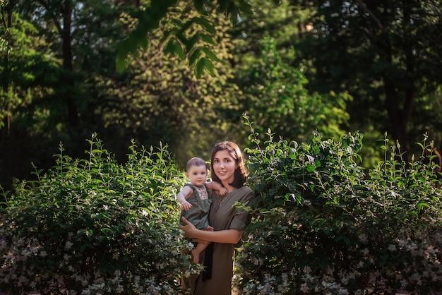 Eine junge frau hält ein kleines baby in den armen. eine schöne mutter geht mit ihrer tochter in einem grünen park in der nähe der jasminbüsche spazieren