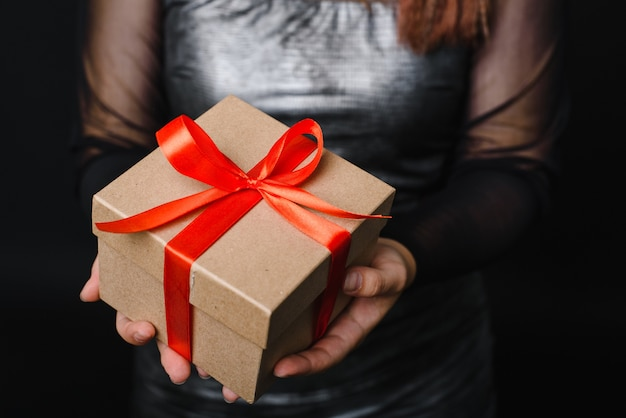Eine junge frau hält ein weihnachtsgeschenk mit einem roten band in den händen. geschenkkonzept für das neue jahr.