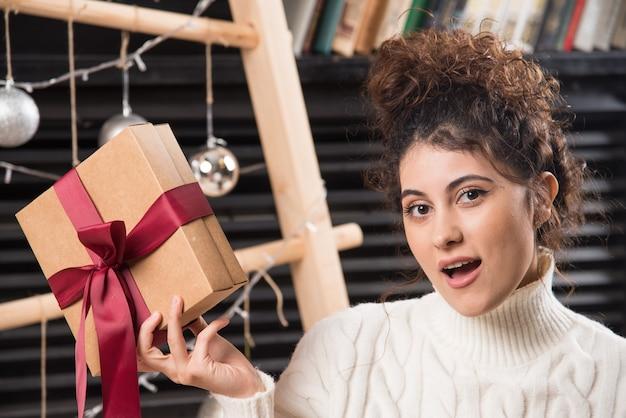 Eine junge frau hält eine geschenkbox mit schleife