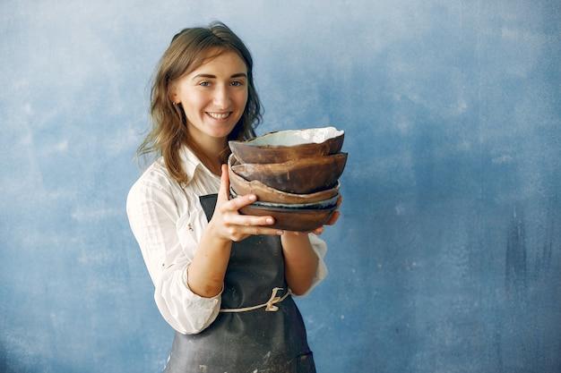 Eine junge frau hält eine keramikschale in den händen