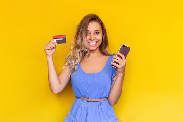 Eine junge frau hält eine plastik-kreditkarte und ein handy in den händen, um online-einkäufe zu bezahlen
