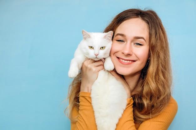 Eine junge frau hält eine weiße katze in den armen.