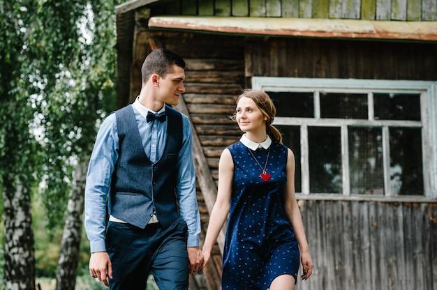 Eine junge frau hält hand ehemann, der an birke nahe einem alten hölzernen stilvollen haus geht.