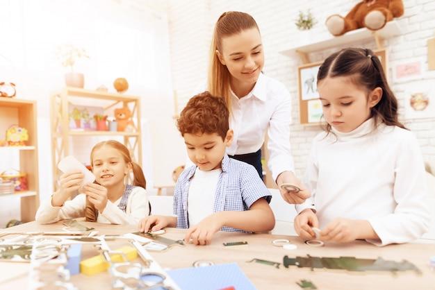 Eine junge frau hilft kindern, teile aus pappe zu falten.