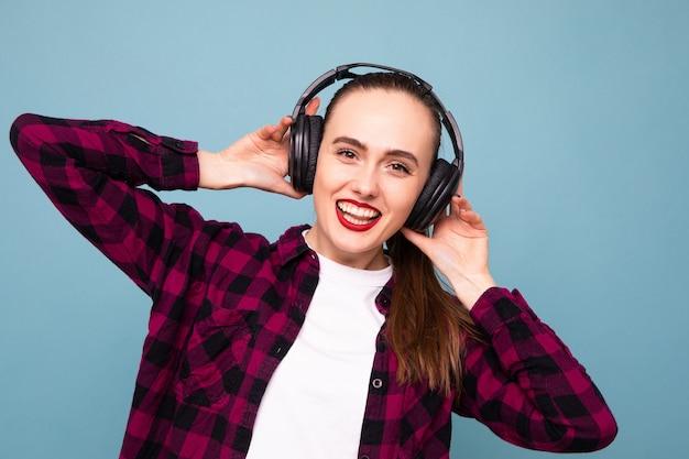 Eine junge frau hört gut gelaunt musik mit kopfhörern