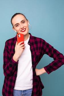 Eine junge frau hört musik von ihrem telefon auf einem blauen hintergrund