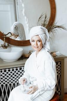 Eine junge frau im bademantel mit einem handtuch um den kopf breitet eine bio-gesichtsmaske in einer schüssel im badezimmer aus.