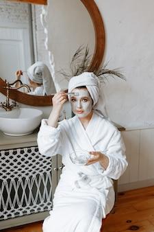 Eine junge frau im bademantel mit einem handtuch um den kopf trägt eine gesichtsmaske im badezimmer auf.