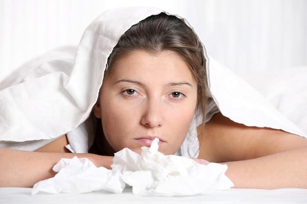 Eine junge frau im bett mit grippe auf weißem hintergrund