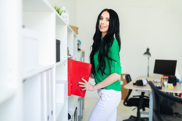 Eine junge frau im büro zieht ordner mit dokumenten heraus.